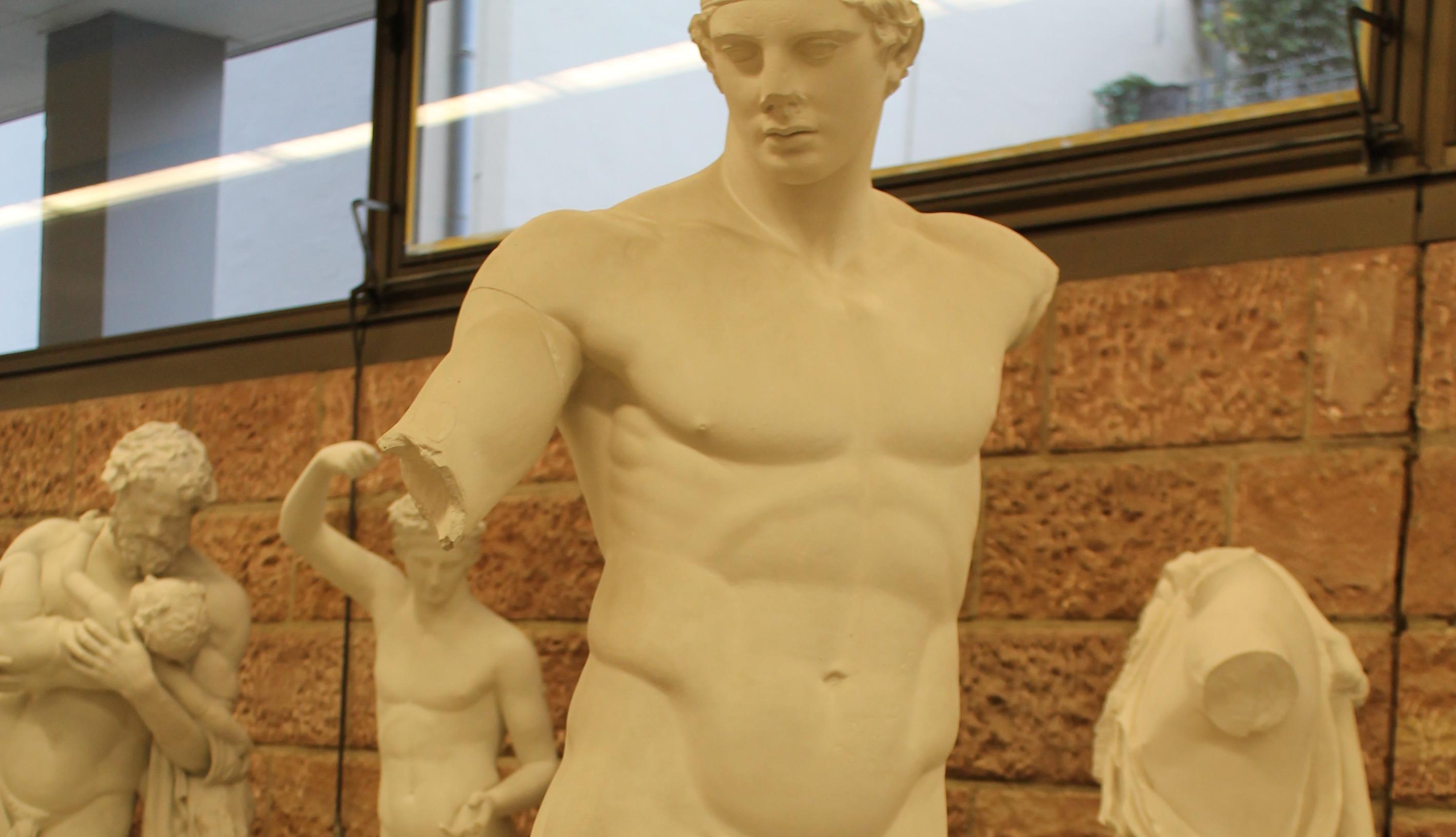 Der stehende Athlet (sog. Diadoumenos): Abguss im Foyer des Instituts für Alte Geschichte. Das Original ist aus Marmor und befindet sich im Archäologischen Nationalmuseum in Athen.   Original aus Marmor in Athen, Archäologisches Nationalmuseum. Gefunden auf der Insel Delos, ursprünglich war er wohl mit Blattgold überzogen. Vorbild der Marmorstatue war die Bronzestatue des Bildhauers Polyklet, entstanden um 420 v.Chr. (Klassische Zeit). Darstellung eines Athleten, der sich ein Band um den Kopf wickelt (daher der Name Diadoumenos), dies ist wohl ein Hinweis auf seinen Sieg. Foto: Christina Deinsberger