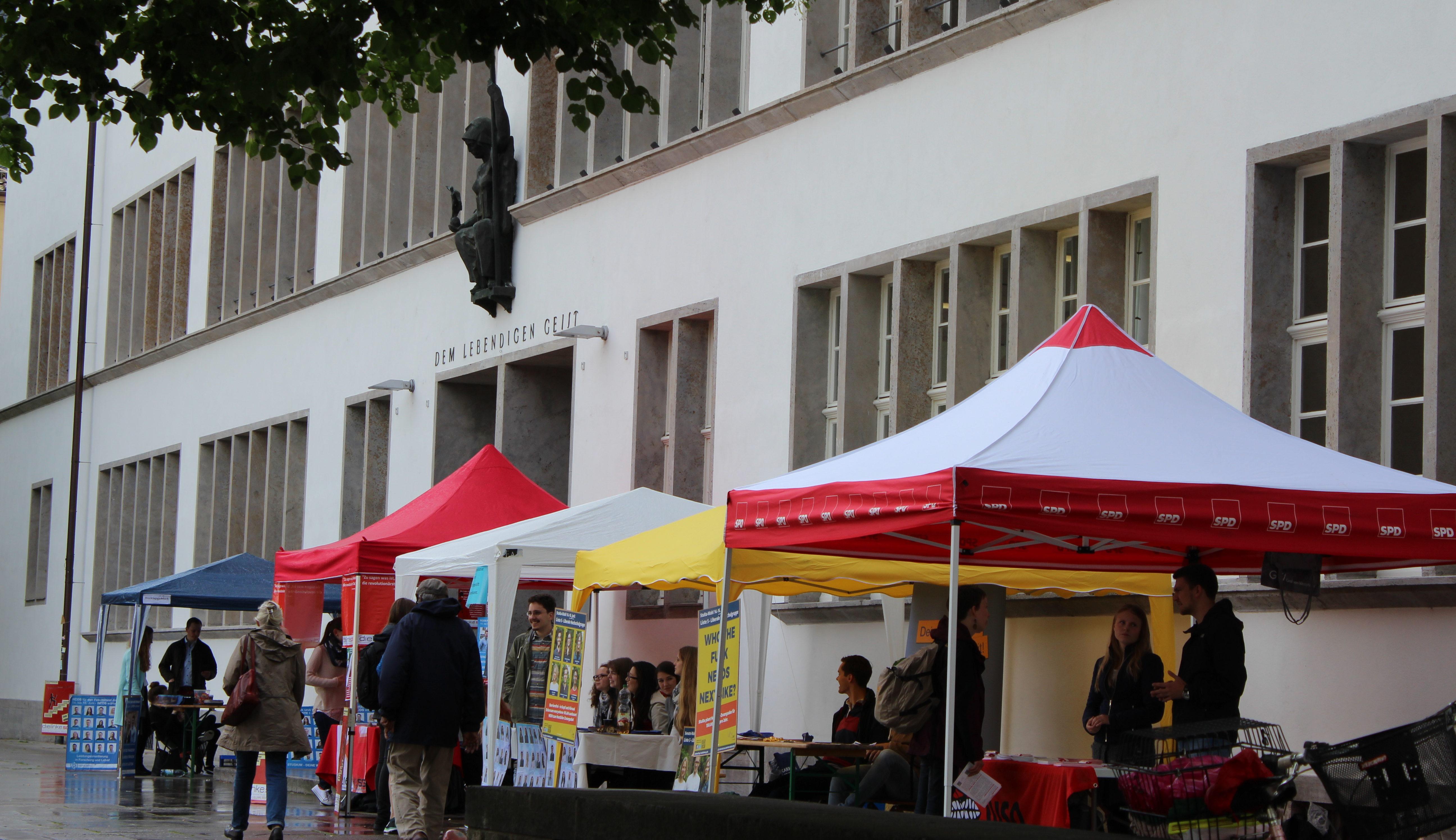 Wahlkampf im Regen. Vor der Neuen Uni ringen die Listen um die Gunst ihrer Wählerinnen und Wähler. Bild: Hannah Lena Puschnig.