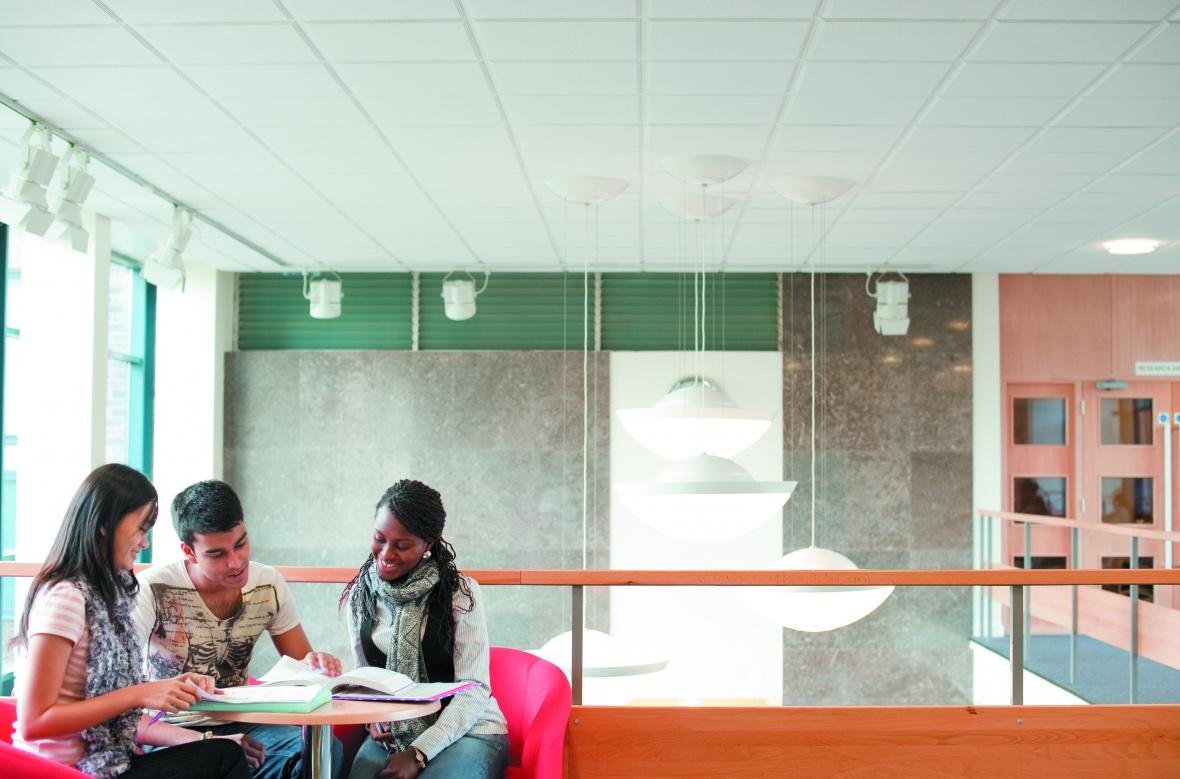 Drei internationale Studierende schauen sich gemeinsam ein Buch an