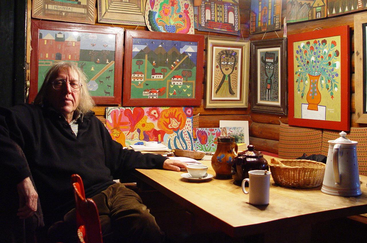 """Egon Hassbecker in seinem Haus in Mülben (Odenwald), umgeben von Werken seiner Sammlung """"primitiver"""" Malerei. Foto: Privatbesitz Familie Hassbecker."""