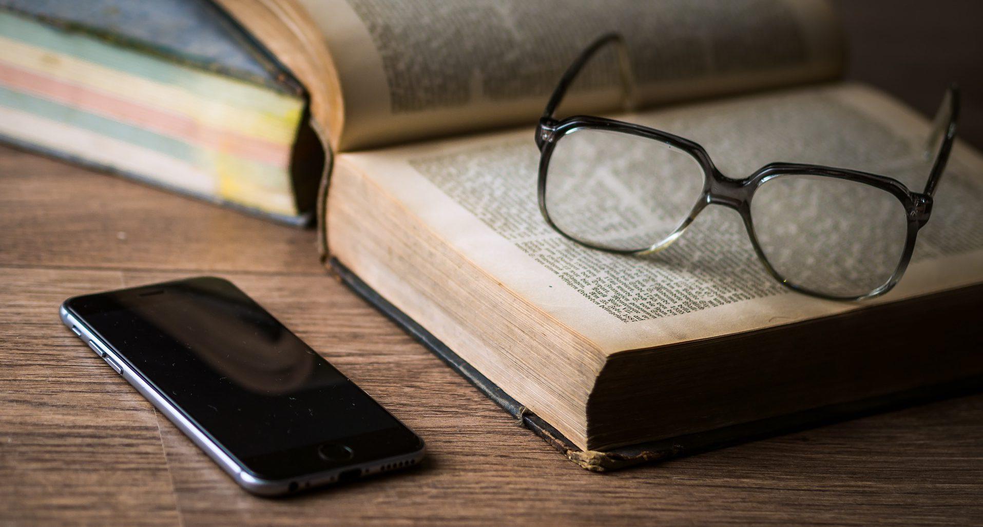 Ein Smartphone liegt neben einem Buch