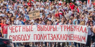 """Bei den Protesten im August halten Demonstrierende ein Banner mit der Aufschrift """"Ehrliche Wahlen. Tribunal. Uneingeschränkte Freiheit."""" hoch."""
