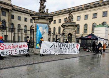"""Berliner Studierende stehen mit Protestplakaten vor einem Universitätsgebäude. Auf einem großen Banner steht """"Zu Verkaufen""""."""